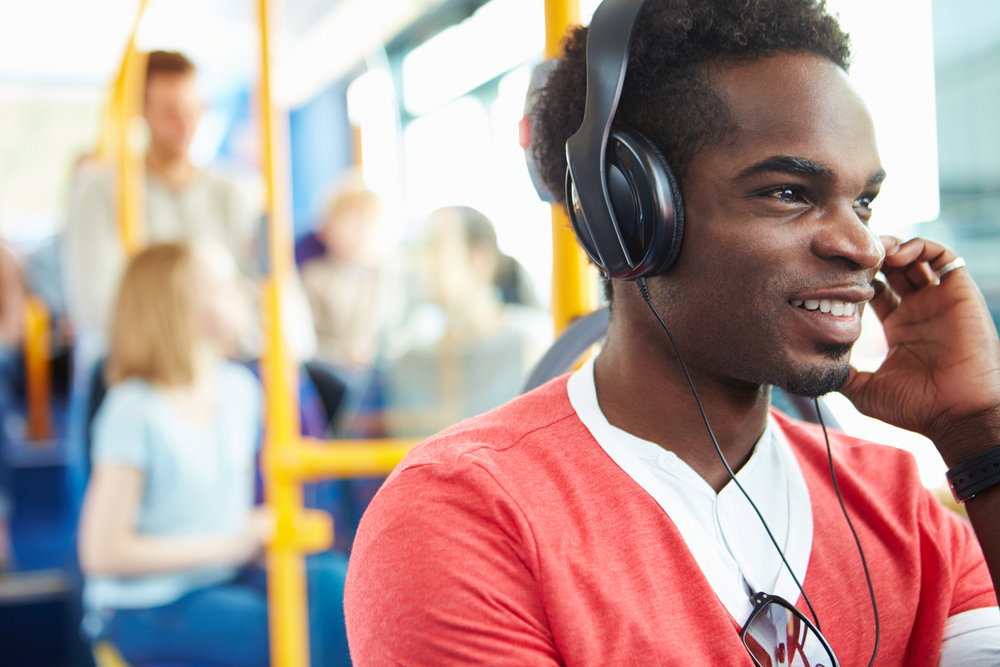 Man with headphones sitting on a bus